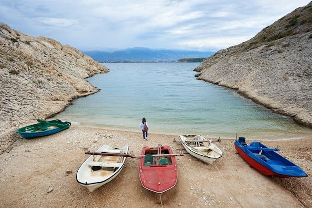 Małe łodzie motorowe na przytulnym wybrzeżu portowym wśród wysokich skalistych brzegów i młodej kobiety turystycznej