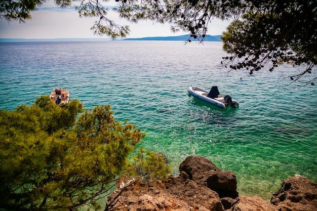 Małe łodzie pływające w pobliżu brzegu w małej wiosce brela, riwiera makarska, chorwacja