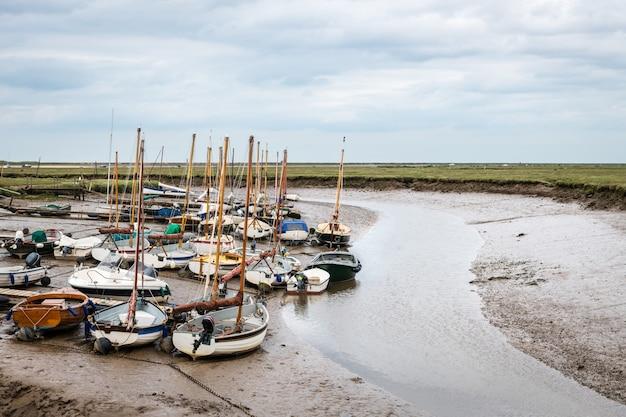 Małe łodzie żaglowe zacumowane w porcie blakeney w norfolk podczas odpływu w pochmurny letni dzień.