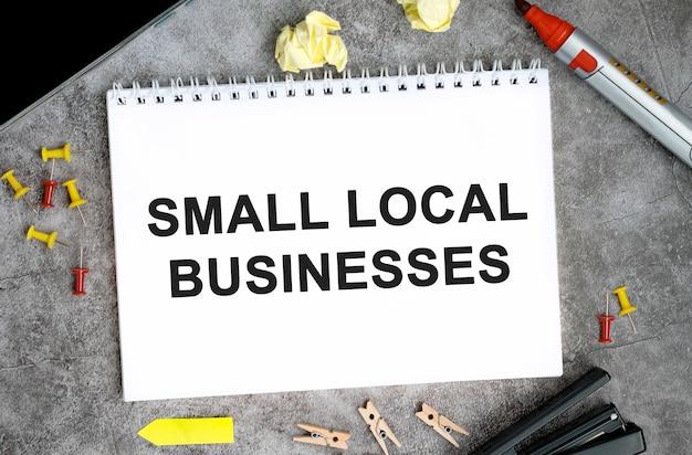Małe lokalne firmy tekst na białym notatniku ze szpilkami, markerem i zszywaczem na betonowym stole
