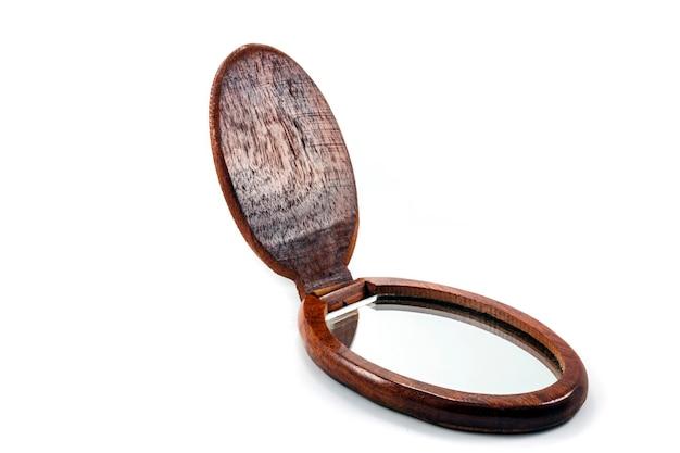 Małe lusterko w drewnianej ramie na białej powierzchni