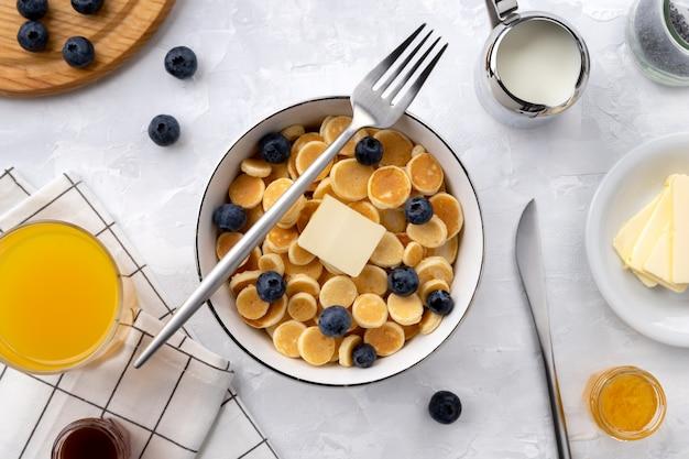 Małe mini naleśniki. domowe śniadanie z jagodami, dżemem i sokiem na szarym tle
