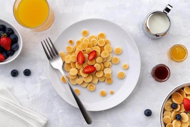 Małe mini naleśniki. domowe śniadanie z malinami, jagodami, dżemem i sokiem na szarym tle