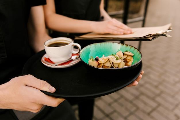 Małe naleśniki w talerzu z jagodami i domową śmietaną z filiżanką kawy na tacy na kelnerze, selektywne focus