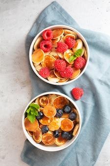 Małe naleśniki z jagodami, malinami, miętą i miodem na śniadanie, widok z góry