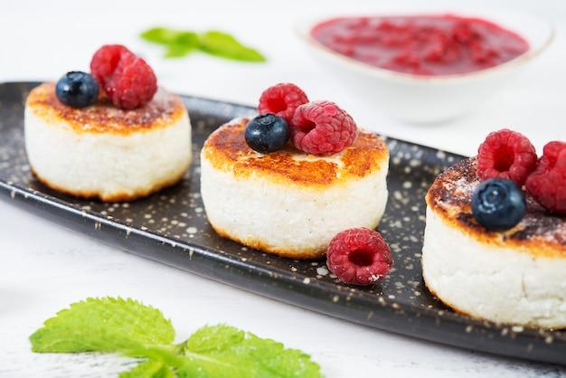 Małe naleśniki z serem z jagodami na białej przestrzeni.