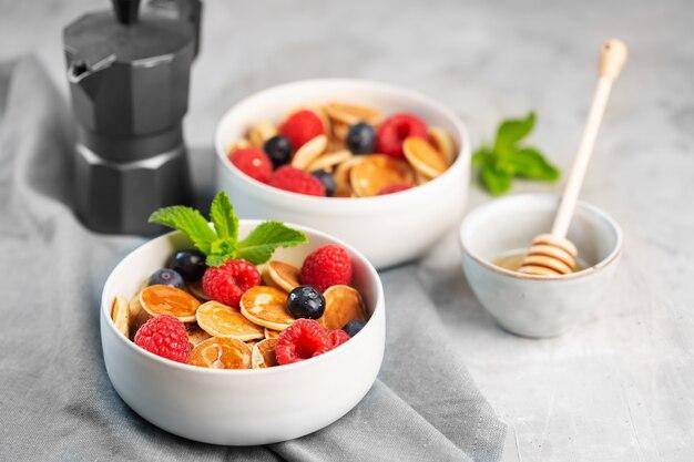 Małe naleśniki zbożowe z jagodami, malinami, miętą i miodem na śniadanie