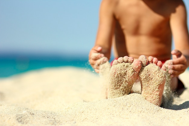 Małe nogi dziecka na piasku na plaży