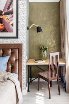 Małe nowoczesne gabinet w sypialni. biurko i krzesło obok łóżka. ściana pokryta zielonym tynkiem dekoracyjnym