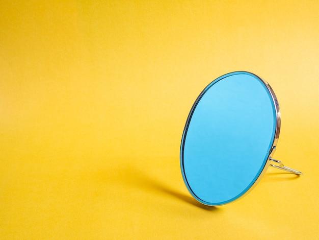 Małe nowoczesne lustro na biurko na żółtym tle