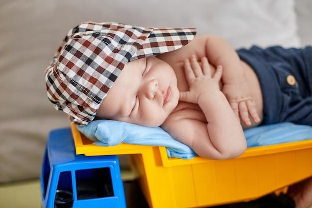 Małe noworodek śpi w ciężarówce zabawki