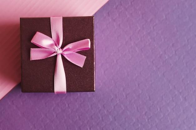 Małe ozdobne pudełko z różową wstążką na fioletowo-różowym tle
