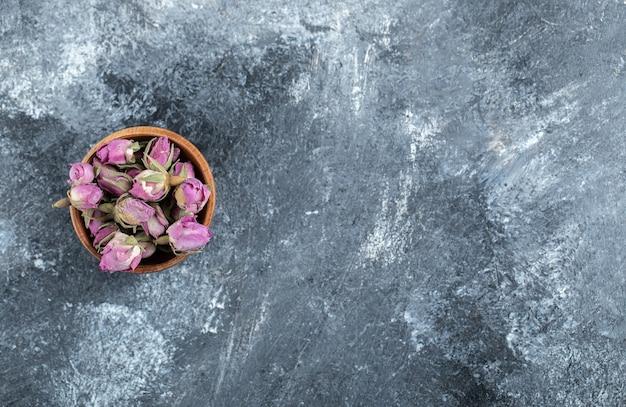 Małe pączkujące róże w drewnianej misce.