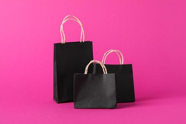 Małe papierowe torby na różowej przestrzeni, miejsca na tekst