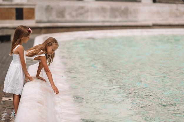 Małe piękne dziewczyny przy fontannie fontana di trevi