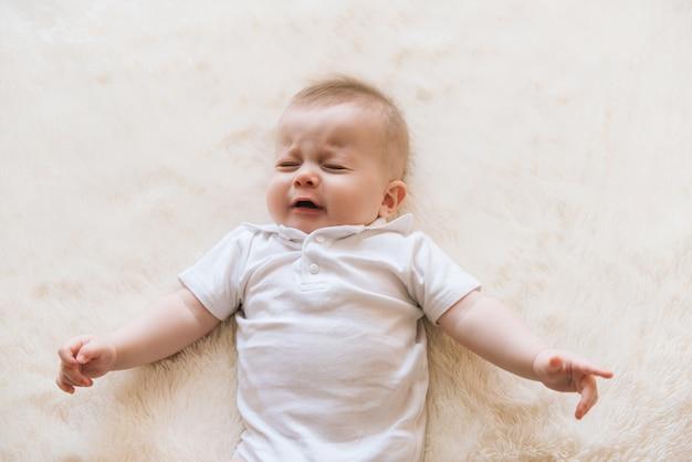 Małe piękne niemowlę noworodek płacze i leży