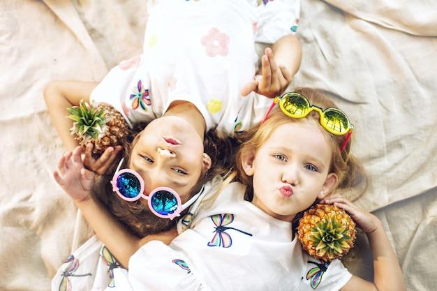 Małe piękne słodkie dziewczyny dzieci w białych sukienkach z ananasami w rękach na tropikalnych roślinach