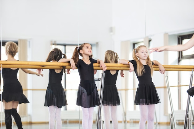 Małe piękne słodkie dziewczyny dzieci w studio trenują z trenerem na lekcji tańca.