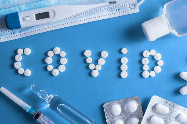 Małe pigułki o różnym kolorze i kształcie ułożone w słowo (covid - 19) na niebieskim tle. pojęcie koronawirusa.