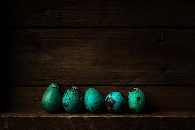 Małe pisanki farbowane nakrapiane na ciemnym drewnianym rustykalnym