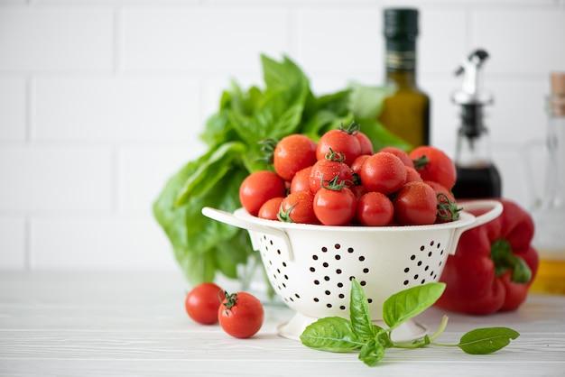 Małe pomidory w durszlaku z bazylią i przyprawami na białej ścianie