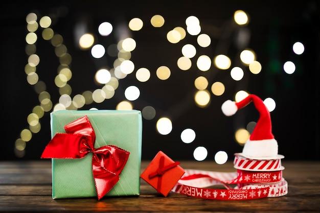 Małe prezenty w pobliżu wstążek i kapelusza bożego narodzenia