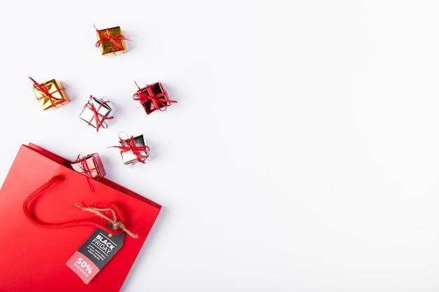 Małe prezenty wychodzące z torby z czarną metką