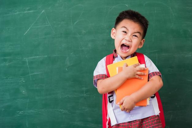 Małe przedszkole chłopiec dziecko w mundurku studenckim z tornister trzymać lub przytulać książki