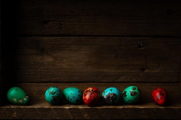 Małe przepiórki barwione pisanki na ciemnym drewnianym rustykalnym