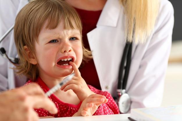 Małe przestraszone dziecko w recepcji lekarza robi zastrzyk insuliny