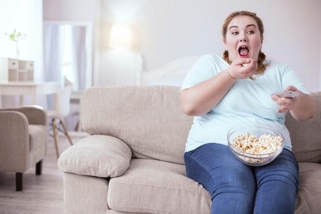 Małe przyjemności. pulchna młoda kobieta otwiera usta i wrzuca do nich garść popcornu
