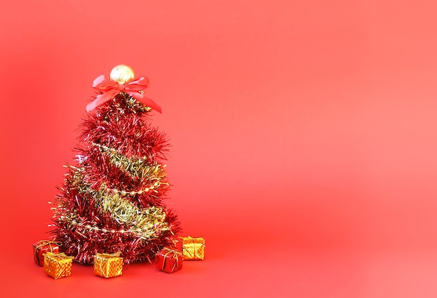 Małe pudełka prezentowe i choinka wykonane z błyszczącej jasnej dekoracyjnej girlandy na czerwonym tle.