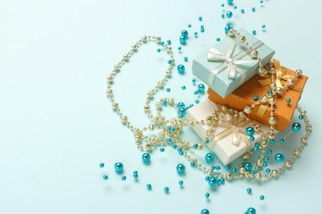 Małe pudełka upominkowe są ułożone na pastelowym turkusowym tle. prezenty świąteczne, błyszczące, błyszczące koraliki ozdoby.