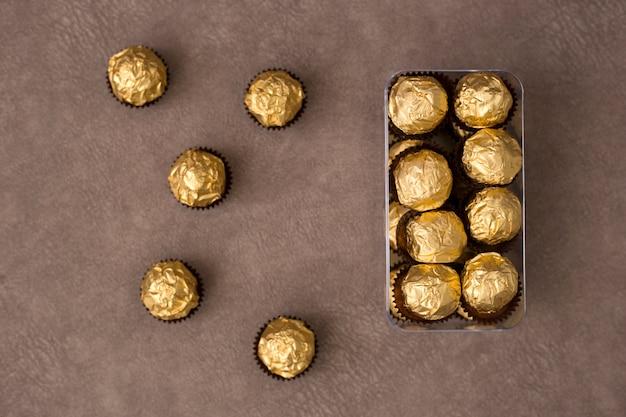 Małe pudełko cukierków czekoladowych w złotej folii stoi na brązowym tle