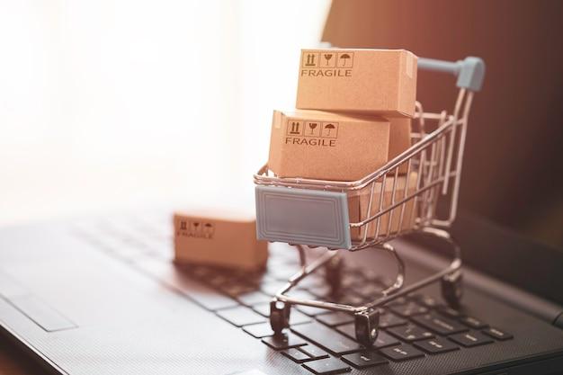 Małe pudełko kartonowe z wózkiem na zakupy na laptopie komputera dla koncepcji zakupów online.