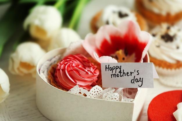 Małe pudełko w kształcie serca z kwiatami i babeczkami z życzeniami happy mother's day