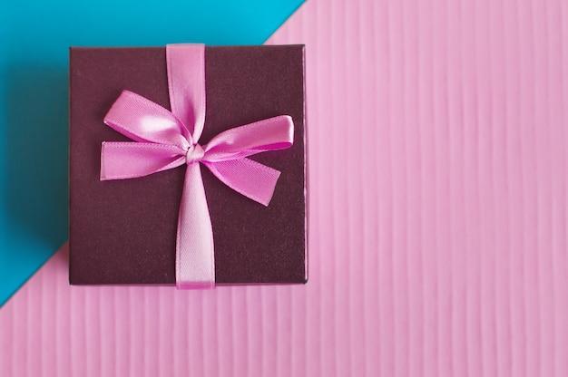 Małe pudełko z różową wstążką i kokardką na kolorowym niebiesko-różowym