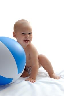 Małe pulchne dziecko pali niebieską zabawkową piłkę w paski