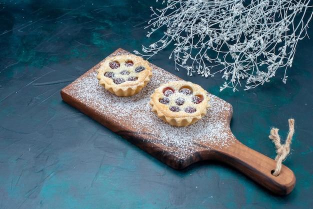 Małe pyszne ciasta z cukrem owocowym w proszku na niebieskim biurku, ciasto biszkoptowe ciasto słodkie cukier