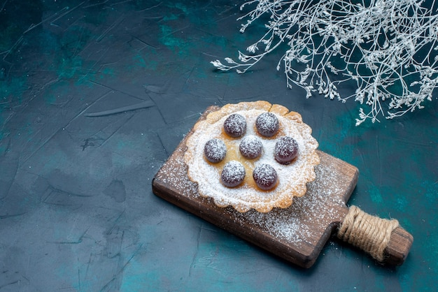 Małe pyszne ciasto z cukrem pudrem i wiśniami na granatowym biurku, słodkie ciastko owocowe