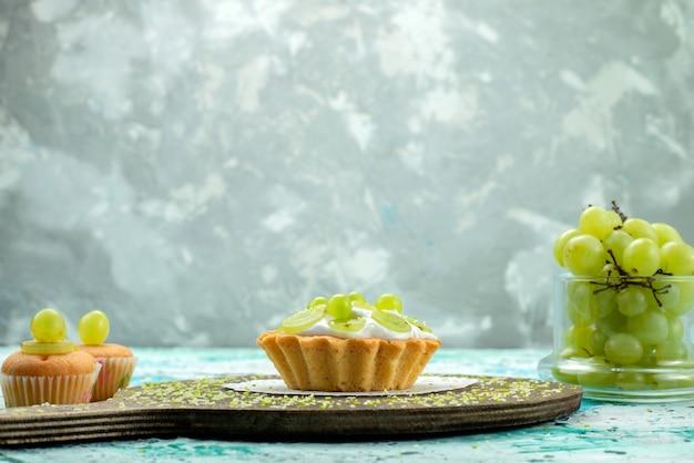 Małe pyszne ciasto z pyszną śmietaną i pokrojonymi i świeżymi ciasteczkami winogronowymi na niebieskim biurku, słodkie ciasto owocowe