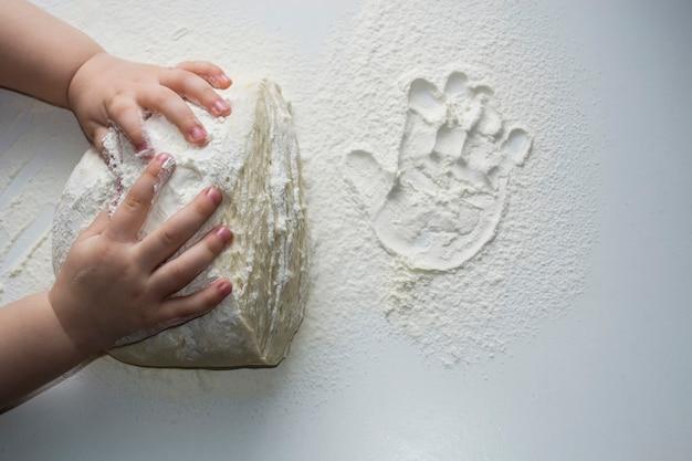 Małe rączki ugniatające ciasto małe dziecko przygotowujące ciasto na podkład dzieci rączki trochę mąki pszennej...