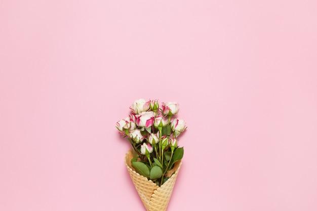 Małe róże w gofra rożku na różowym tle, kopii przestrzeń. leżał w minimalistycznym stylu.