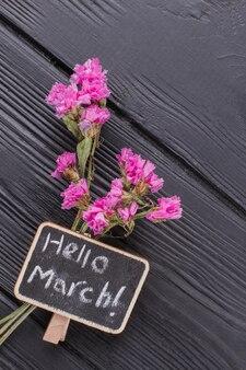 Małe różowe kwiaty na ciemnym tle drewnianych. widok z góry z bliska. witaj marszu.