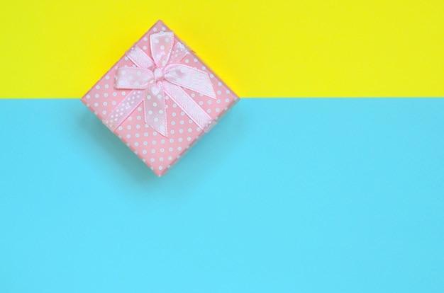 Małe różowe pudełko leży na fakturze moda pastelowy niebieski i żółty