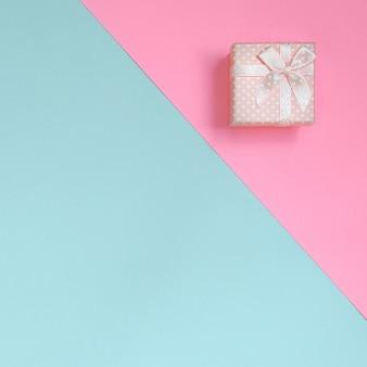 Małe różowe pudełko leży na papierze pastelowym niebieskim i różowym