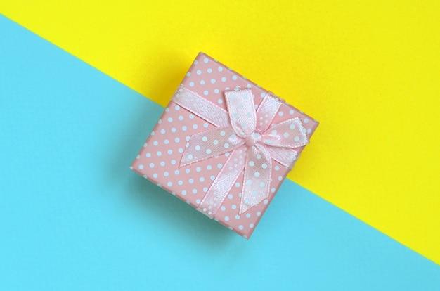 Małe różowe pudełko leży na pastelowym niebieskim i żółtym papierze