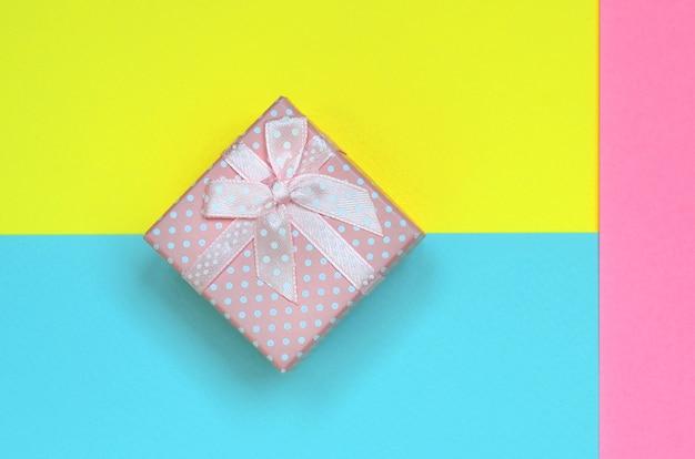 Małe różowe pudełko prezentowe na papierze pastelowym niebieskim, żółtym i różowym