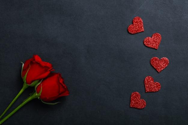 Małe serca i czerwone róże na czarno