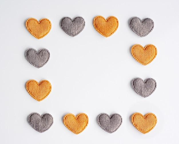 Małe serduszka tekstylne w żółte i szare paski na białym tle